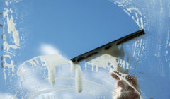 32147702 - window cleaner using a squeegee to wash a window