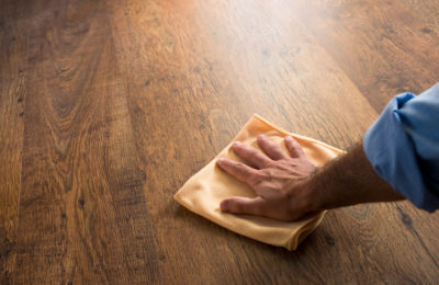 32522138 - male hand cleaning and rubbing an hardwood floor with a microfiber cloth.