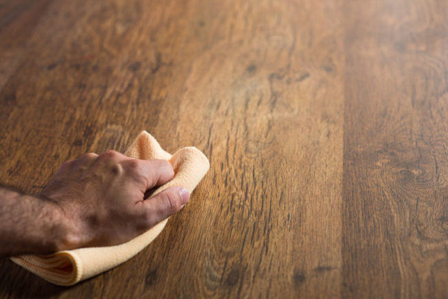 31527377 - male hand cleaning and rubbing an hardwood floor with a microfiber cloth.
