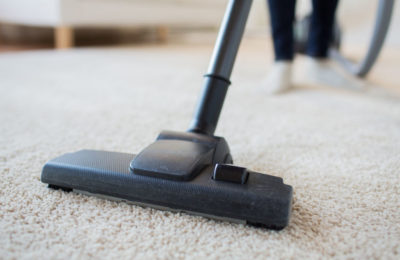 38663111 - people, housework and housekeeping concept - close up of woman with legs vacuum cleaner cleaning carpet at home