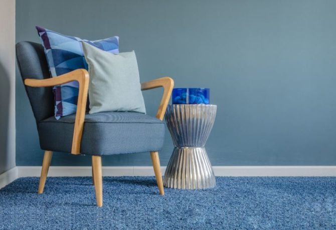 37699196 - wooden chair with blue color pillow on carpet in living room