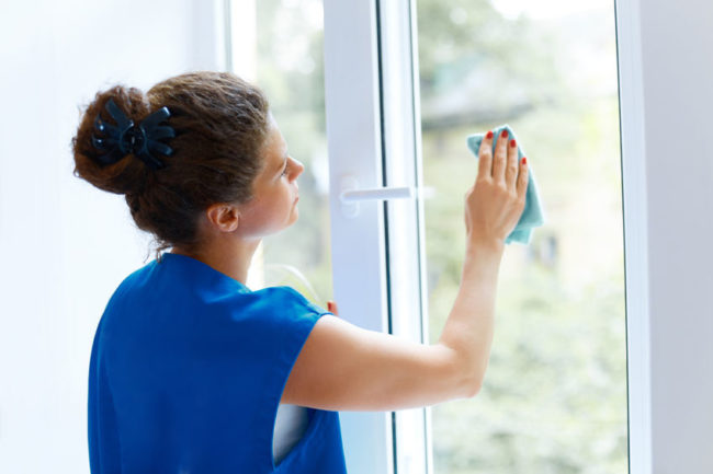 45743850 - young woman cleaning window glass. cleaning company worker