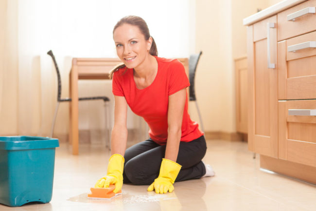 27044304 - young girl washing floor in kitchen. beautiful housewife doing cleaning and smiling