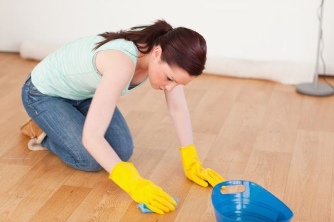10206155 - gorgeous red-haired woman cleaning the floor while kneeling at home