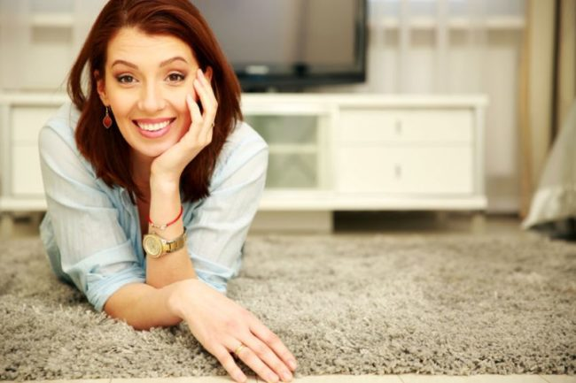 26067445 - smiling woman lying on the floor at home